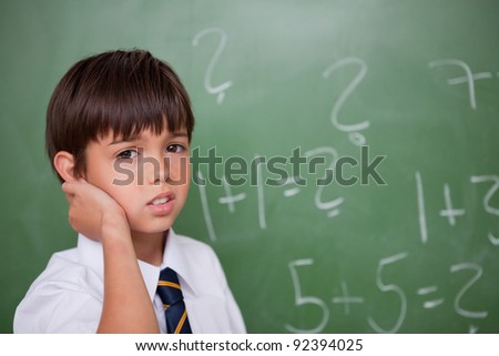 Confused schoolboy thinking while scratching the back of his head in a classroom - stock photo