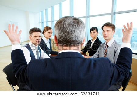 Confused specialists looking at their senior leader with misunderstanding - stock photo