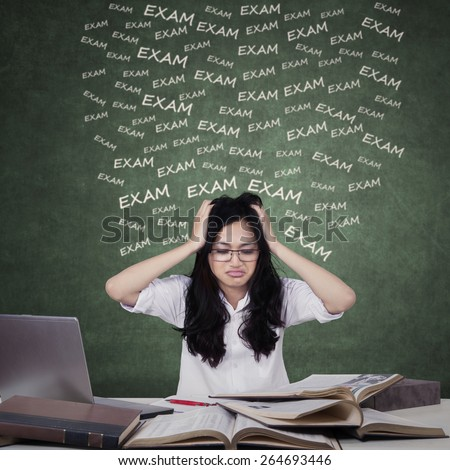 Confused teenage girls preparing for exam while studying with laptop and textbooks - stock photo