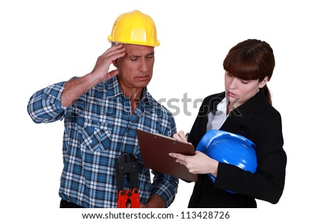 Confused tradesman watching an engineer writing on a clipboard - stock photo