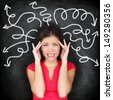 Confused woman - people feeling confusion and chaos. Indecisive, disorientated and bewildered woman stressed with headache over decision making. Girl in 20s on blackboard background. Asian / Caucasian - stock photo
