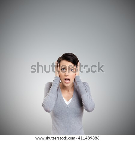 Confused woman puts her hands on the head, isolated on grey - stock photo