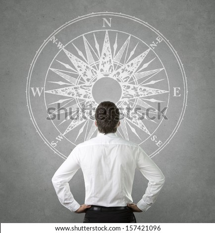 Confused, young businessman looking at compass wind rose drawn on the concrete wall - stock photo