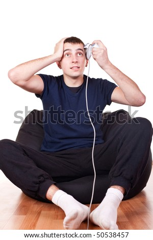 confused young man holding video game controller - stock photo