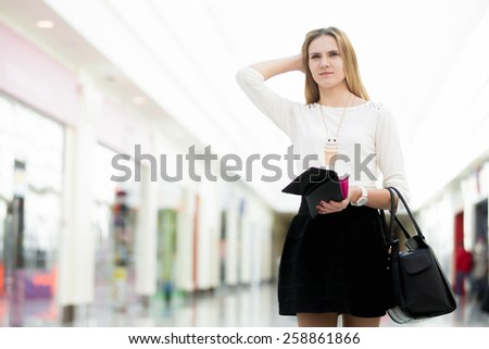 Confused young woman out of money holding opened wallet in mall, deciding on shopping, economy, tight budget, broke, copyspace - stock photo