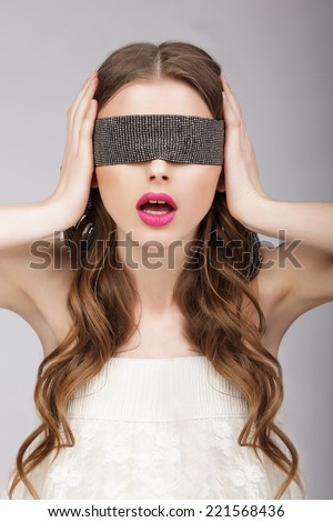 Confusion. Woman holding Headband on her Head - stock photo
