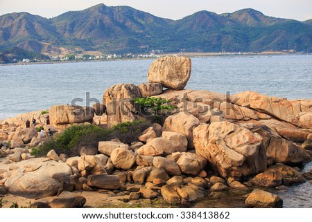 conglomeration of different stones in form of animal from beach towards sea water against distant hilly tropical island - stock photo