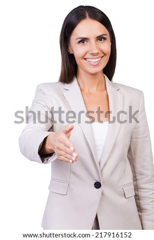 Congratulations! Confident young businesswoman in suit stretching out hand for shaking and smiling while standing against white background - stock photo
