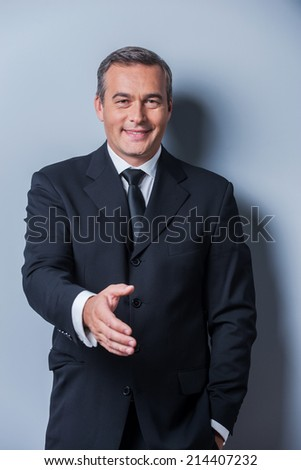 Congratulations! Portrait of cheerful mature man in formalwear stretching out hand for shaking while standing against grey background - stock photo