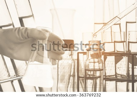 Conical flask in scientist hand with lab glassware background, Laboratory research concept,Ancient image process style - stock photo