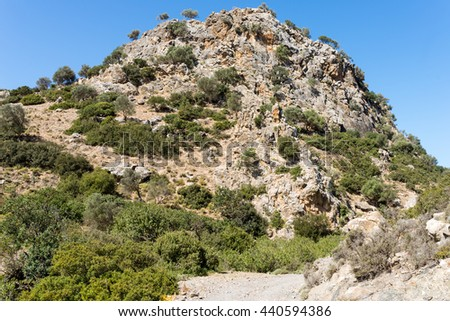 Conical hill on the hiking trail down from Pitsidia to Matala. The huge rock is a landmark, isolated and the only one in this part of Crete. The geological formation looks like a volcanic plug