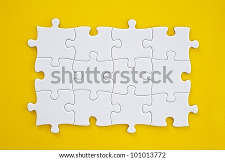 Connected blank puzzle pieces isolated on a yellow background. - stock photo