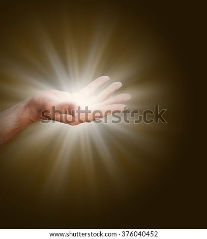 Connecting to the Divine Source - a male hand with palm open  glowing with light energy on a dark warm brown background with plenty of copy space - stock photo