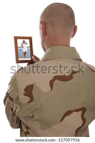 Conscript  marine looks at the photo of the girlfriend isolated over a white background - stock photo