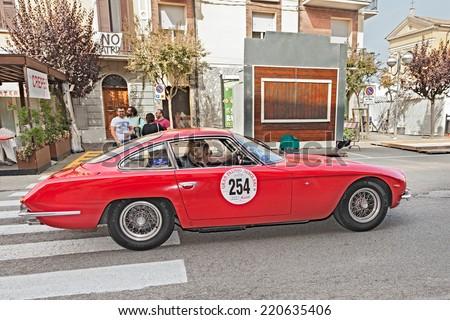 """CONSELICE, RA, ITALY - SEPTEMBER 21: the female crew Grimaldi Ciaran on a first model Lamborghini, a 350 GT (1965) in historic race """"Gran Premio Nuvolari"""" on September 21, 2014 in Conselice, RA, Italy - stock photo"""