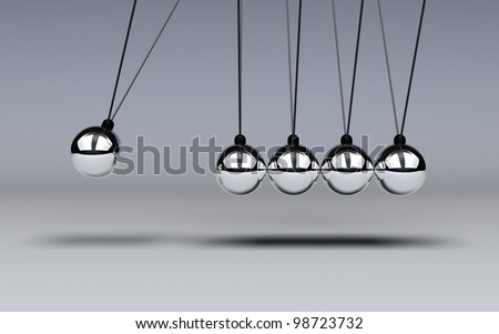 Conservation of energy is demonttrated with a Newtons Cradle in motion - stock photo