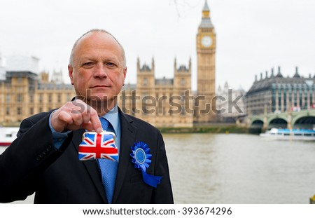 Conservative Politician Holding Union Jack Purse Outside The Houses Of Parliament In London. - stock photo