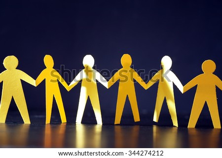 Consolidation concept. Yellow paper men in a row on dark background
