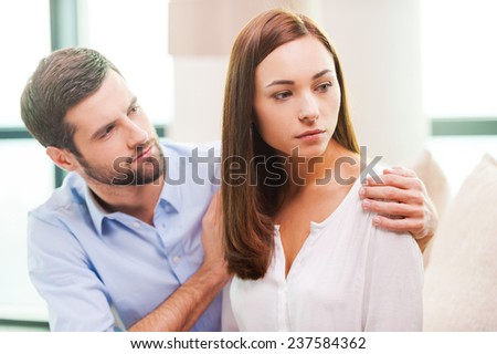 Consoling his depressed girlfriend. Depressed young woman looking away while man sitting behind her on the couch and consoling her - stock photo