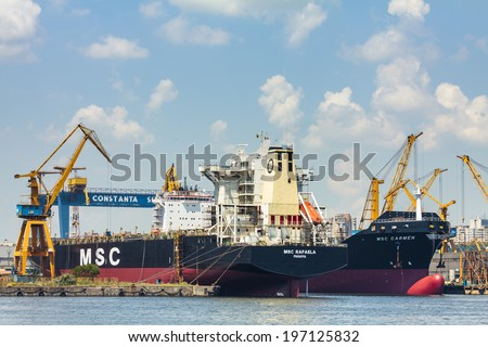CONSTANTA, ROMANIA - MAY 27, 2014: Bulk cargo ships docked under crane bridge in industrial port quay of Constanta, the largest on the Black Sea and the 18th largest in Europe.