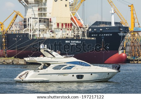 CONSTANTA, ROMANIA - MAY 27, 2014: Modern luxurious white motor yacht floats in the bay of commercial port of Constanta city, the largest port on the Black Sea and the 18th largest in Europe. - stock photo