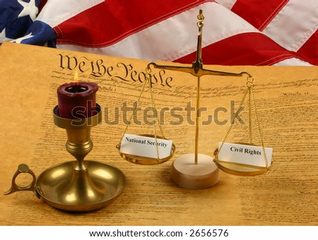 """Constitution, candle, American Flag, and scales with """"national security"""" and """"civil rights"""" in the balance - stock photo"""