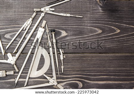 Constructing steel metal compasses on a dark wooden background in disorder. Useful for backdrop for professional greeting cards for engineers, architects, teachers and designers - stock photo