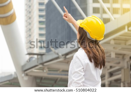 Construction and maintenance concept, Female architect in yellow helmet pointing finger with city background