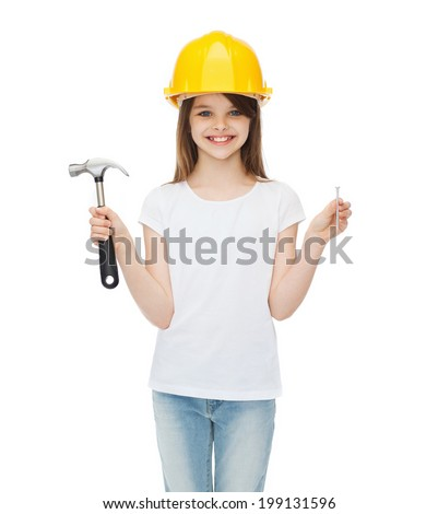 construction and people concept - smiling little girl in protective helmet with hammer and big nail - stock photo