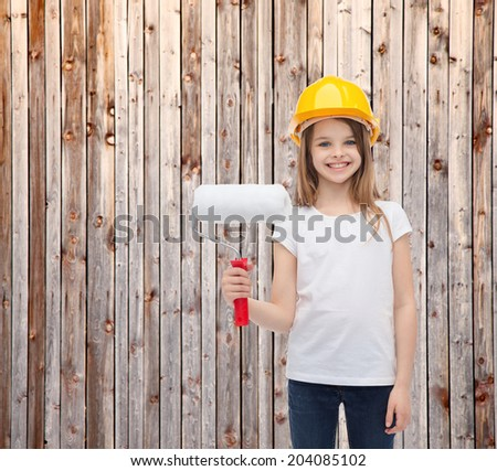 construction and people concept - smiling little girl in protective helmet with paint roller - stock photo