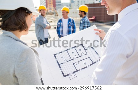 construction, architecture, business, teamwork and people concept - close up of architects with blueprint at building site - stock photo