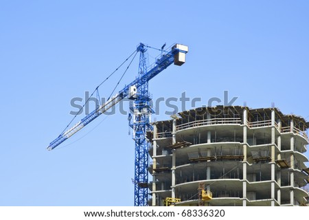 Construction area: crane and incomplete high-riser against blue sky background