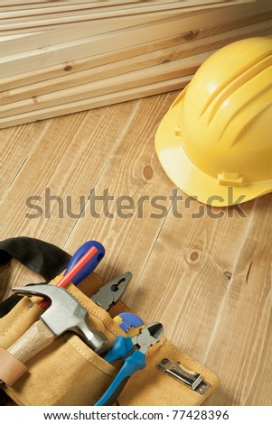 Construction background. Yellow helmet and tool belt on wooden floor. - stock photo