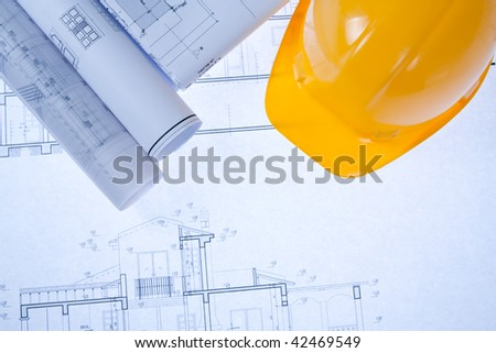 Construction Blue print and yellow hard hat - stock photo