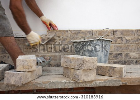 Construction. Bricklayer worker building walls. Space for text. - stock photo