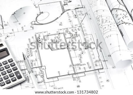 Construction building plans with calculator and pencil - stock photo