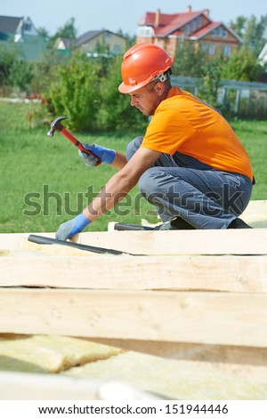 construction carpenter worker nailing wood board with hammer on roof installation work - stock photo