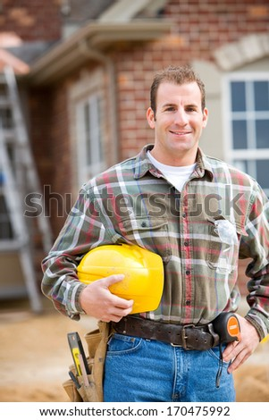 Construction: Cheerful Home Builder with Safety Helmet.