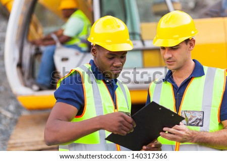construction co-workers discussing about work plan construction site - stock photo