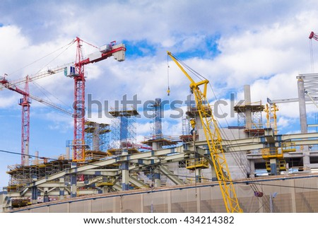 Construction crane and building construction site against blue sky - stock photo