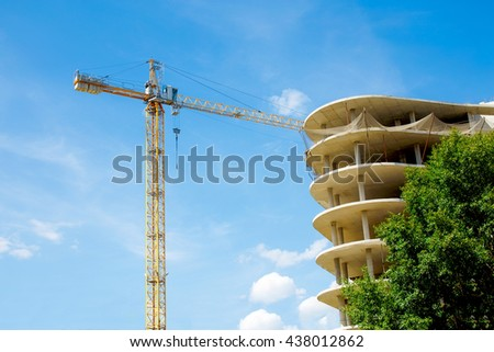 construction crane and unfinished high-rise building. construction of hotel, office building or a shopping mall on a background of blue sky - stock photo
