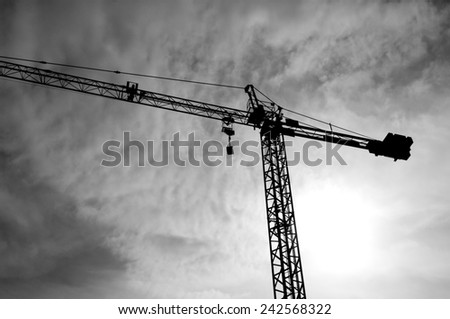 Construction crane bottom view in operation with cloud sky background. Black&White photo. - stock photo