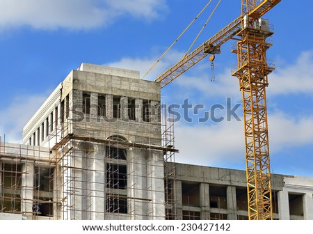Construction crane on the background of rising white building - stock photo