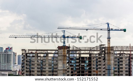 Construction crane on top of building and cloudy sky