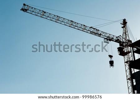 Construction crane  silhouette over sun - stock photo