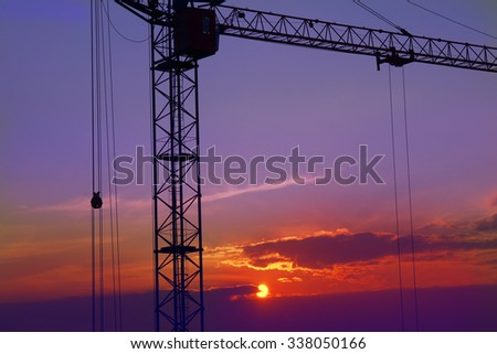 construction crane stands against a background of a sunset - stock photo