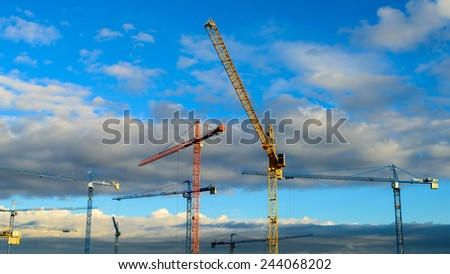 Construction cranes against beautiful stormy sky - stock photo