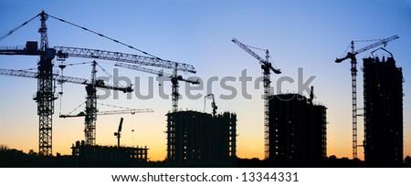 construction cranes silhouette sunset - stock photo