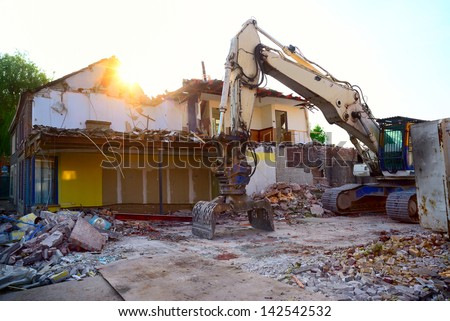 Construction/demolition site with excavator machine, partly demolished buildings and piles of rubble. - stock photo
