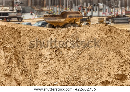Construction dirt pile at worksite. Mound of sandy soil, rocks, and pebbles. Blurred dump truck and new building foundation and concrete pylons in background.  - stock photo